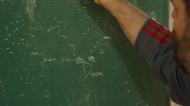 Coach drawing out play on chalkboard — ストックビデオ