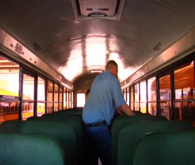 Man walking through empty schoolbus — Stok video