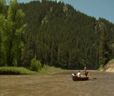 Driftboat in River with mountains — Stockvideo