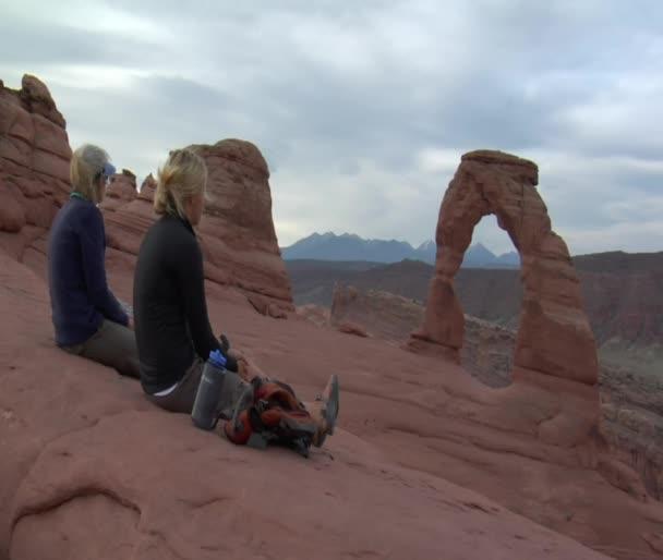 Dos señoras se sientan en la roca y el agua potable — Vídeo de stock