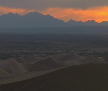 ATV rider crosses Sand Dune with gorgeous mountains sunset — Vídeo de Stock