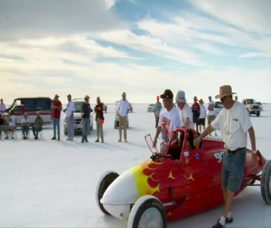 Men push streamlined racecar on Bonneville salt Flats — Stock Video