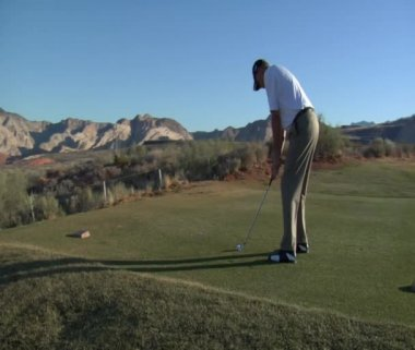 Man tees off with iron on desert golf course — Stock Video