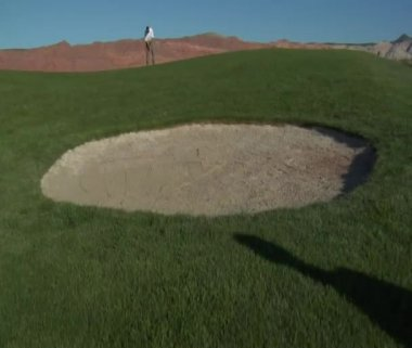 Man putting on desert golf course — Stok video