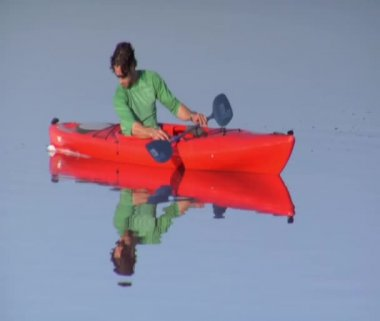 Man in orange kayak paddles on Lake — Stok video