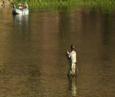 Young man flyfishing in slow motion with drift boat in background — Stock Video