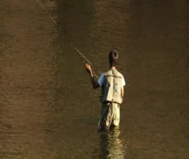 Young man flyfishing in colorful water — Stock Video