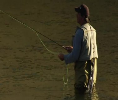 Man flyfishing in hip waders in calm water — Stock Video