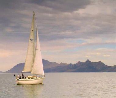 A sailboat glides on calm water near mountains — Vídeo de Stock