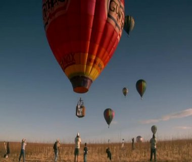 Colorful hot air balloon liftoff with spectators taking photos — Stock Video #34541155