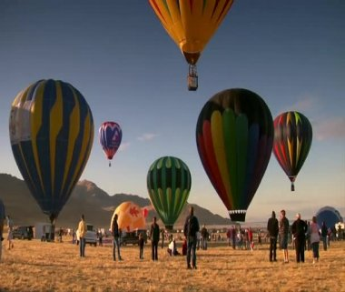 Spectators watch as hot air balloons ascend into the sky — Stock Video
