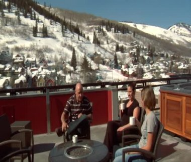 People drink coffee enjoy sunny winter weather on the rooftop in Park city Utah — Stock Video