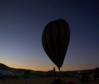 Silhouette of a hot air balloon being filled in the early morning — Stock Video