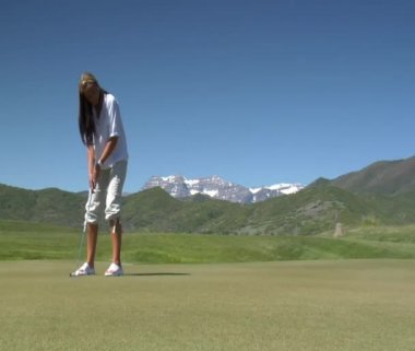 Woman putts on golf green course — Stock Video