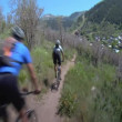 Mountain bikers fly down dusty Summer trail — Stock Video #36343817