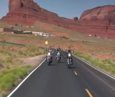 Three bikers on a redrock desert highway — Stock Video