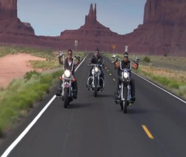 Three bikers on desert highway, mesas behind — Stock Video
