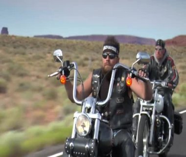 Three motorcyclists ride down desert highway — Stock Video