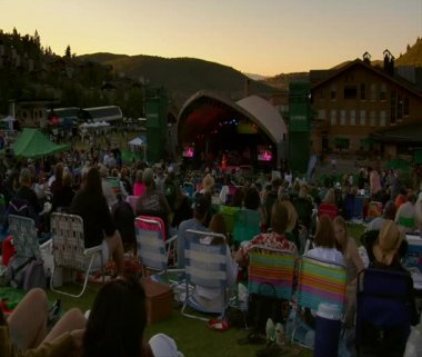 Crowd in lawn chairs watches outdoor concert at sunset — Stock Video