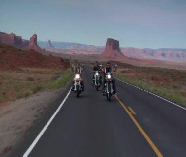 Three bikers on a winding open desert highway — Stock Video