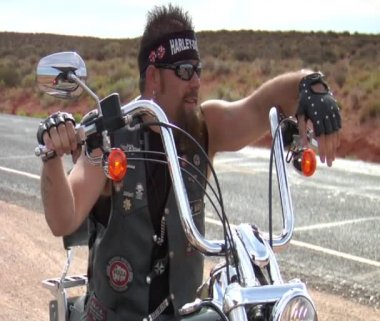 Sarcastic-looking Harley rider leans on handlebar — Stock Video