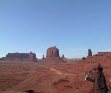 A cowboy on his horse rides to a Vista of Monument Valley — Stock Video