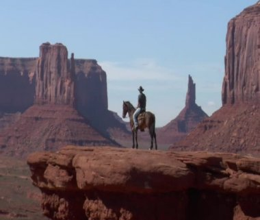 Long zoom shot of cowboy, horse, and Monument Valley — Stock video