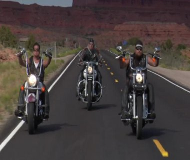 Three bikers on a desert highway, mesas behind — Stok video