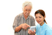 Friendly nurse cares for an elderly woman — Stock Photo
