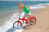 Girl Riding a Bike on the Beach — Stock Photo