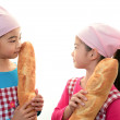Smiling girls holding bread — Stock Photo