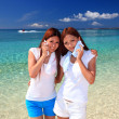 Young women on the beach enjoy sunlight — Stock Photo