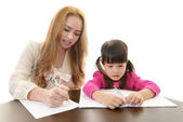 Little girl studying with teacher — Stock Photo