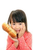 Little girl holding a bread — Stock fotografie