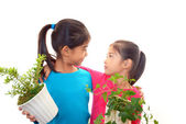 Smiling Asian girls with plants — Stock Photo