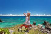 Kız sahilde bir bisiklet sürme — Stok fotoğraf