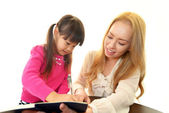 Little girl studying in English with teacher — Stockfoto