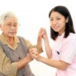 Friendly nurse cares for an elderly woman — Stock Photo #22003825