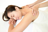 Beautiful woman having relaxing massage on her back in spa salon — Stock Photo