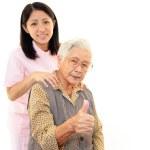 Friendly nurse cares for an elderly woman — Stock Photo #22348299