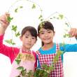 Stock Photo: Smiling Asian girls with plant