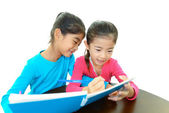 Happy girls studying at the desk — Stock Photo
