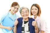 Friendly nurse with elderly woman — Stock Photo