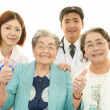 Smiling Asian medical staff with old women — Stock Photo #28839777