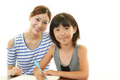 Girl studying with mother — Stock Photo