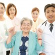 Smiling Asian medical staff with old women — Stock Photo #29099953