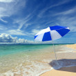 Beach umbrella on a sunny beach with the blue sea in the background. — Stock Photo
