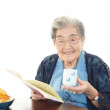 Old woman reading her book — Stock Photo
