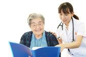 Usmívající se asijské lékař a starší žena — Stock fotografie