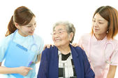 Smiling Asian medical staff with old woman — Stock fotografie